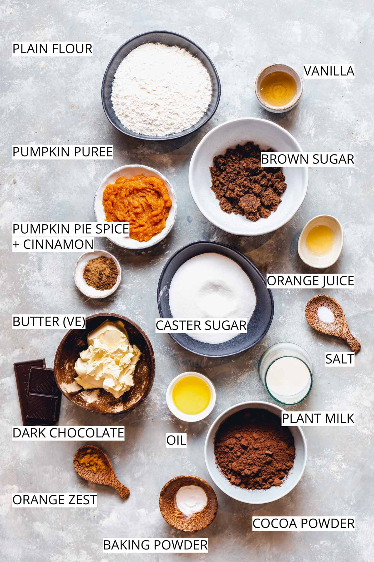All ingredients needed to make vegan pumpkin brownie placed on a flat grey surface.