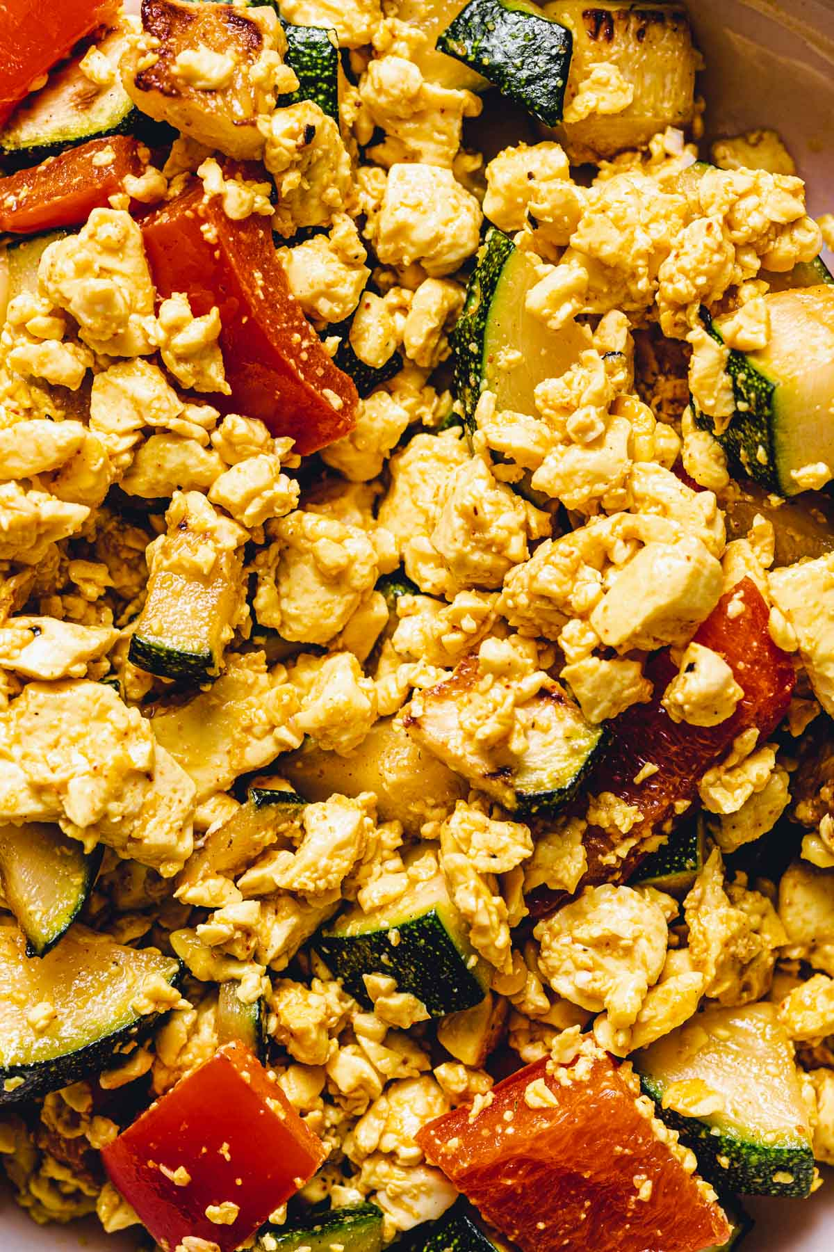 A close-up image of scrambled tofu with courgette and peppers.